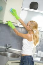 Young woman making damp cleaning at domestic kitchen