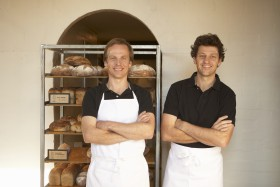 Two male bakers wearing aprons standing with arms crossed, portrait